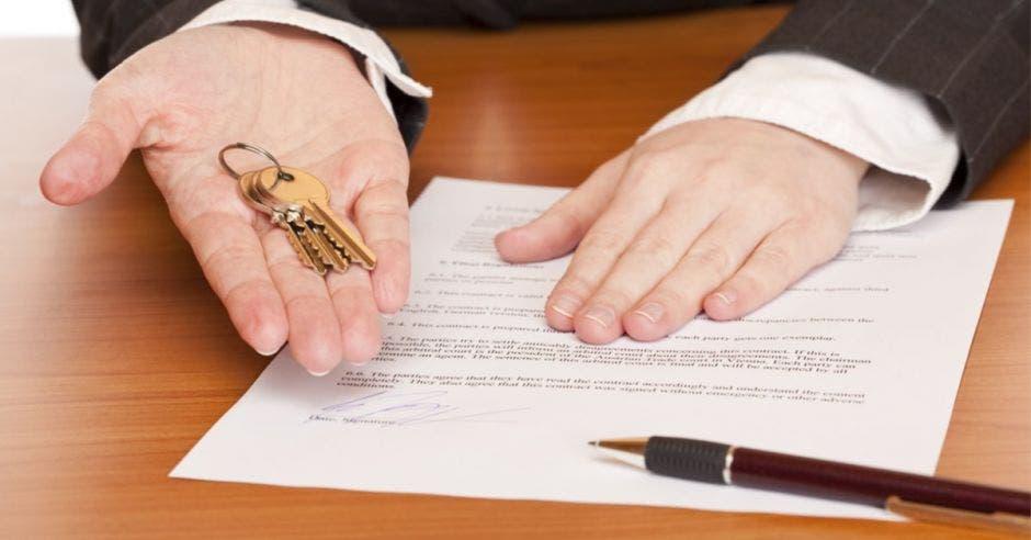 Una persona ofreciendo un contrato, las llaves y un lapicero para firmar