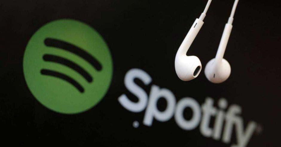 Dos audífonos cuelgan frente al logo de Spotify