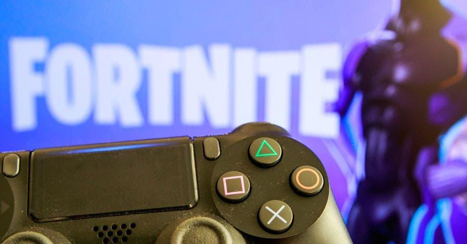 Un control de PS4 frente al logo de Fortnite