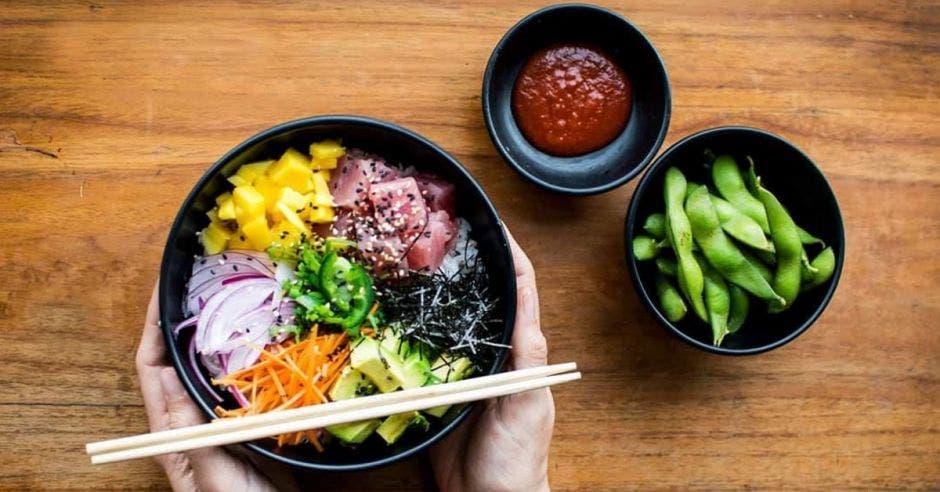 Tres bowls, uno con el poke, otro con salsa especial y uno con edamames