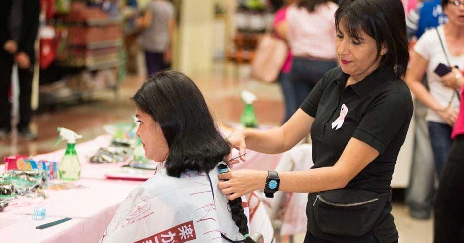 mujer cortándole el cabello a una señora