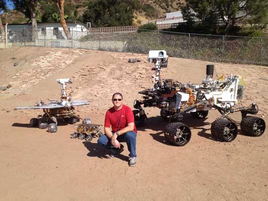 Alex Mora, técnico aeroespacial del Laboratorio de Propulsión a Chorro de la NASA, posa con varios Mars Rover.