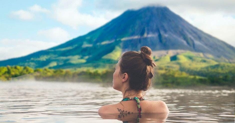 mujer en aguas termales mirando un volcán