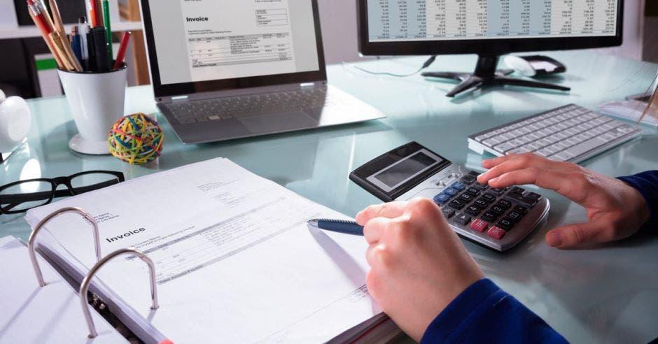 Una computadora con una factura electrónica y alguien haciendo cuentas con la calculadora y una factura impresa