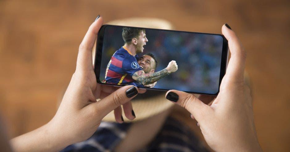 Una mujer sostiene un celular viendo un partido