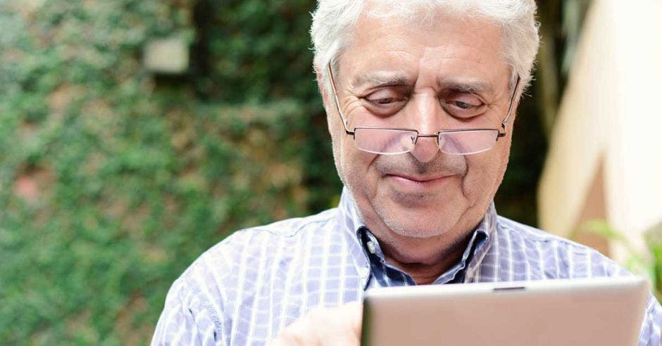 Un adulto mayor manipula una tablet