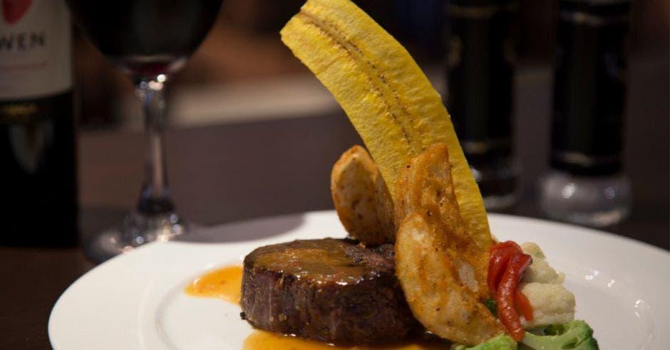 Lomito en un plato acompañado unos plátanos y brócoli