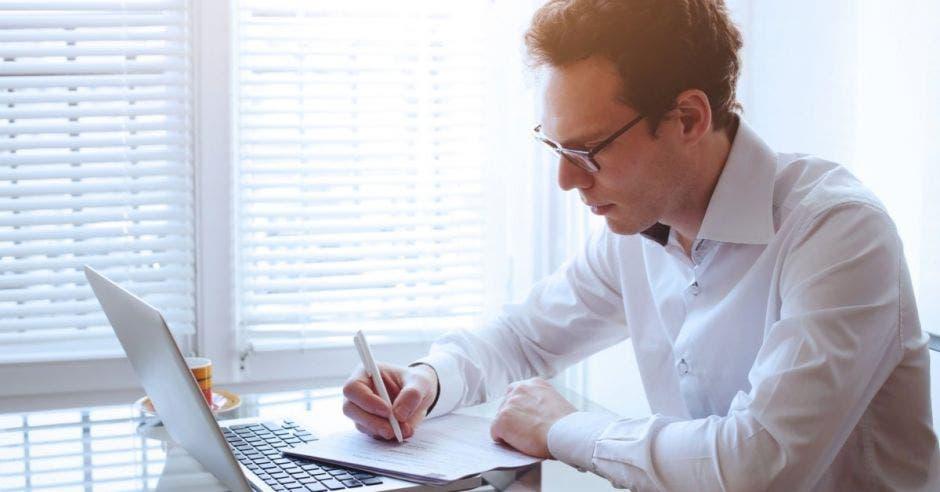 Un hombre revisando el computador mientras escribe en algunos papeles que tiene en su escritorio