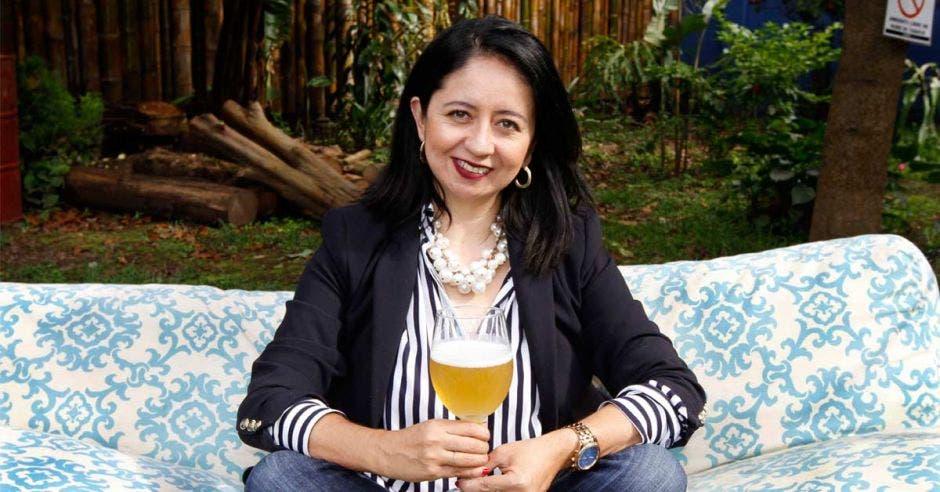 La organizadora Mónica Mendoza posa con una copa llena de cerveza