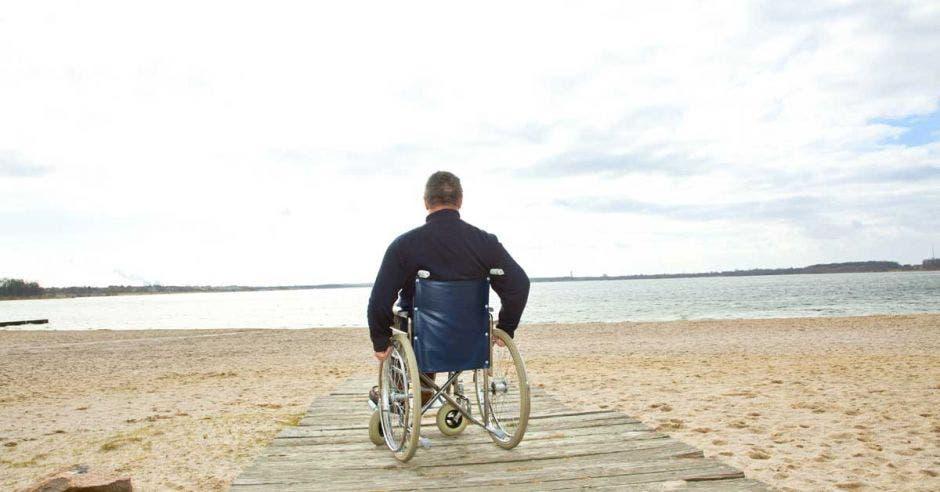 persona en silla de ruedas en la playa