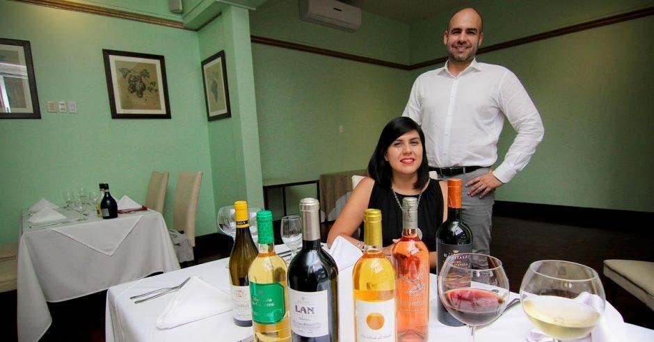 José Salom y Mariana Aguilar posan frente a una mesa con varias botellas de los productos que tratan en una mesa