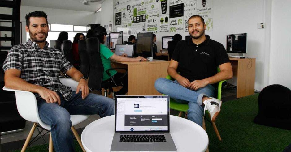 Luis Fernández y Joel Tinoco sentados en su oficina, frente a una computadora