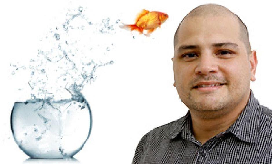 Una foto del autor Carlos Bejarano con una pecera al lado y un pez brincando hacia él