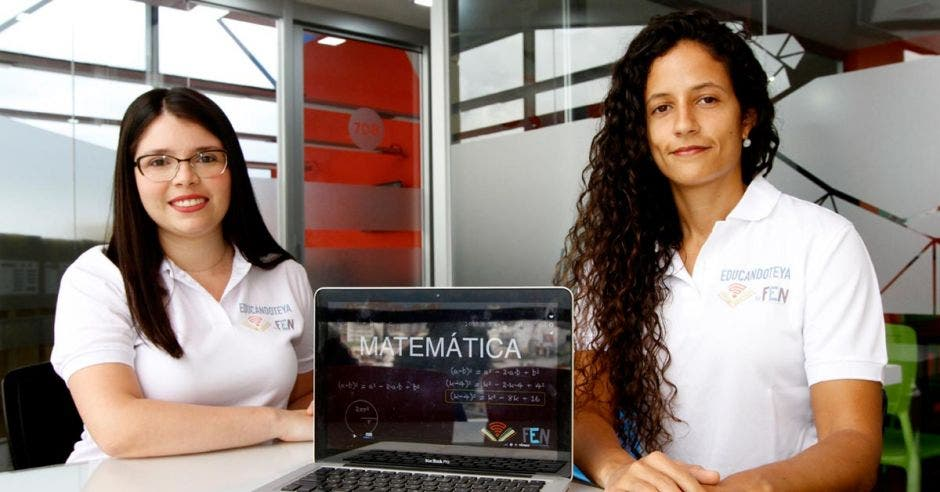 Silvia Leiva, encargada de Mercadeo de la Fundación Educando Niños y María Pia Salinas, directora general, posan con una computadora.