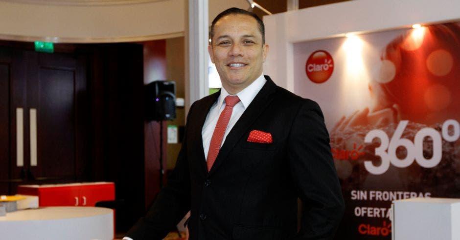 Óscar Chacón posa junto a un stand de la marca Claro durante la Expo IT Comm