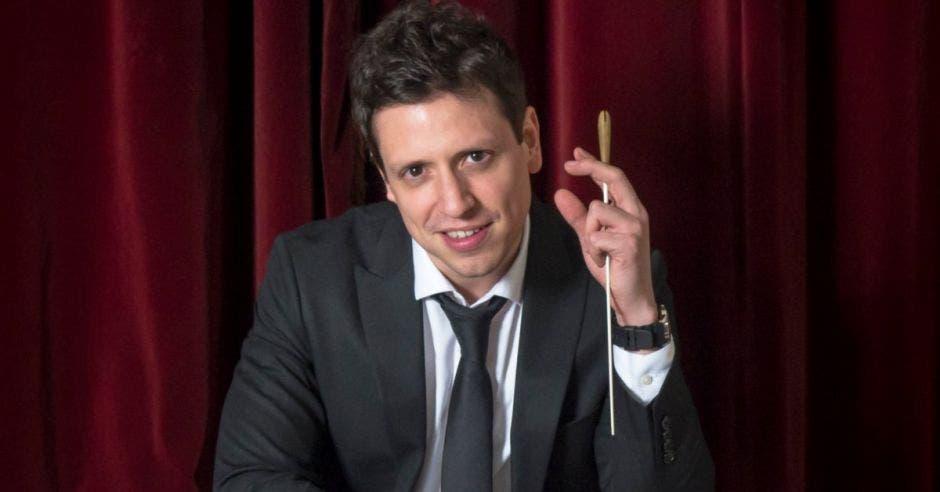 El director con un saco y corbata, con la batuta en su mano izquierda
