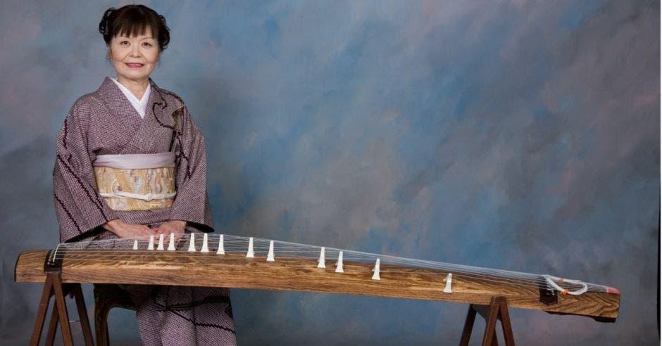 Yoshiko Nishimura con ropa japonesa sentada frente al instrumento koto
