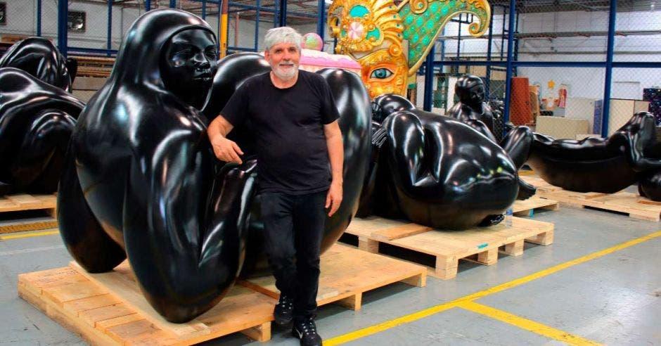 El artista apoyado en una de las esculturas de color negro