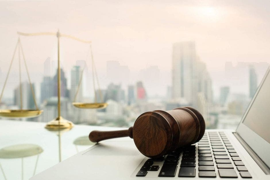 Una computadora  con un mazo de juez y una balanza de justica a lado