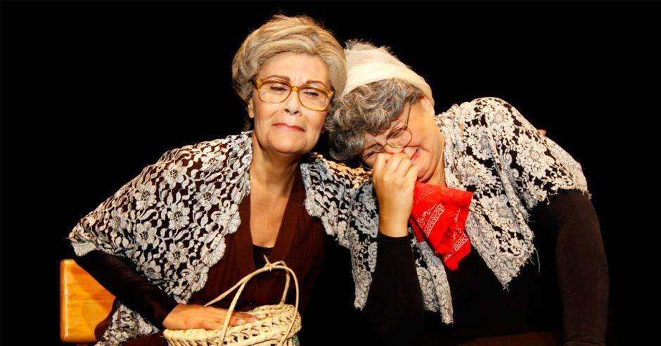 Marcía y María vestidas de viejitas haciendo que lamentan algo