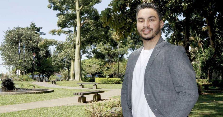Fernando Arce posa en un parque con un blaser color gris