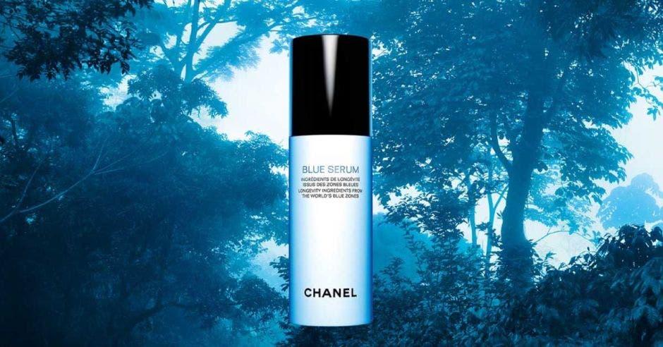 Imagen de la botella de Blue Serum de Chanel sobre el fondo de un bosque