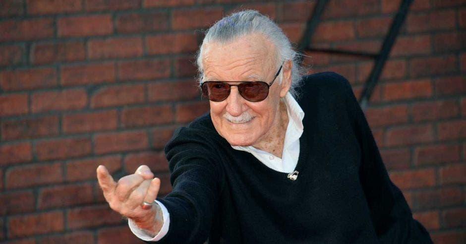 Stan Lee haciendo una señal con sus manos, vestido de negro
