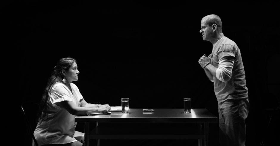 Un hombre y una mujer en una mesa, de perfil, en blanco y negro, como discutiendo, con dos vasos de agua en la mesa