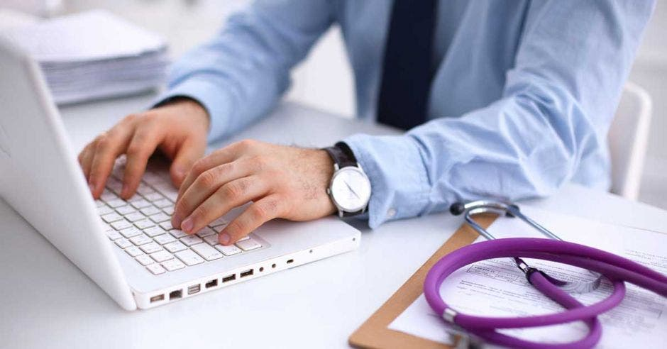 Un doctor revisa expedientes en su computadora