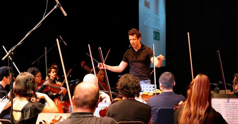 El director Paolo Bortolameolli con una camisa casual dando instrucciones frente a la orquesta