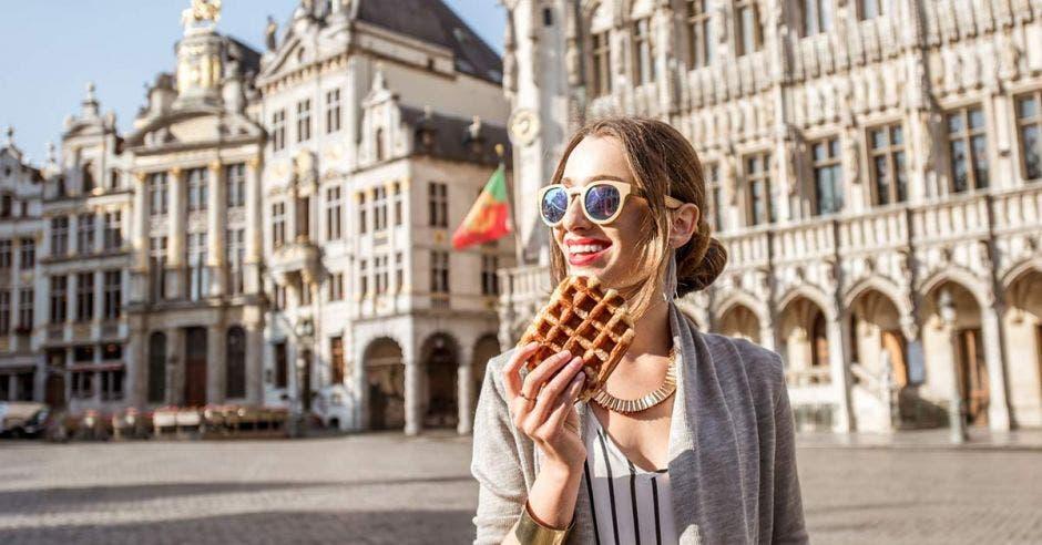 Una mujer sonriendo con un Waffle en la mano, en el fondo unos edificios en Bélgica