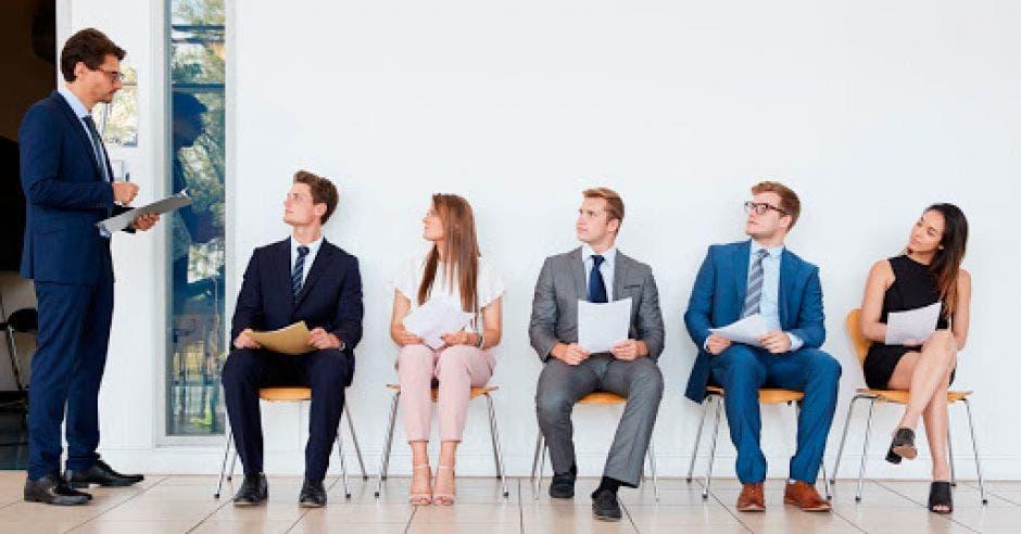 Tres hombres y dos mujeres vestidos formal, escuchan las instrucciones de un entrevistador