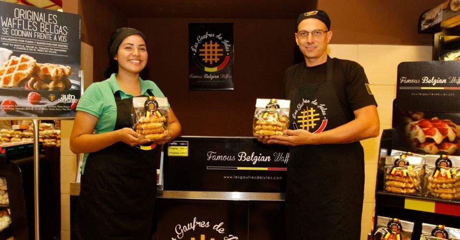 Uno de los socios Julien Groosse junto a una de las vendedoras con los waffles en sus manos