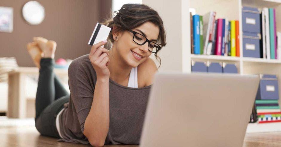 mujer haciendo compras por Internet, frente a una computadora y con una tarjeta en la mano