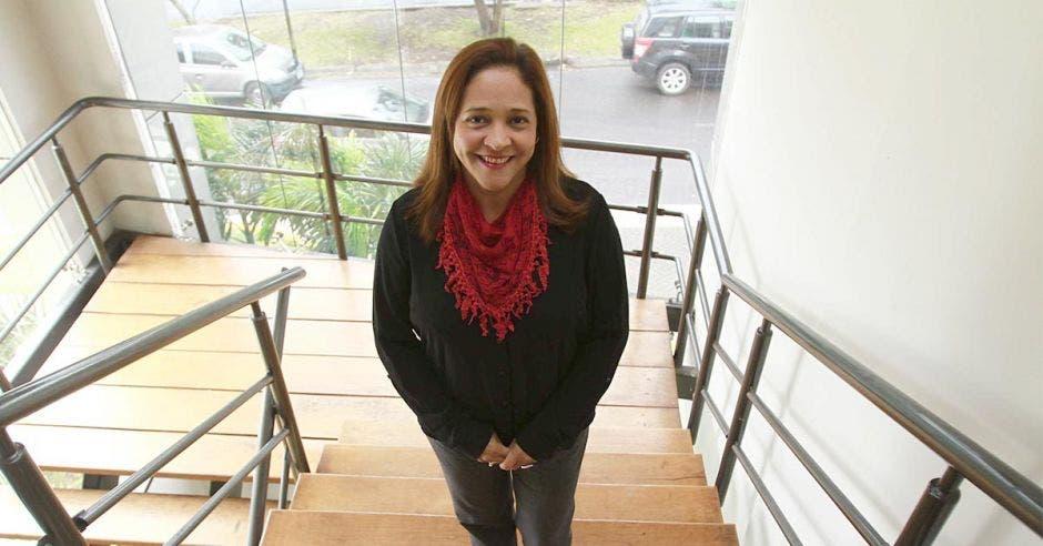 La gerente mujer de pelo castaño con una blusa negra manga larga y una bufanda roja
