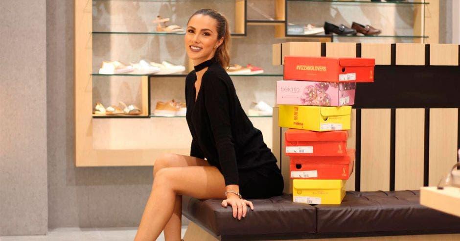Karina Ramos luciendo un vestido negro con algunos zapatos de fondo
