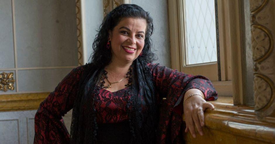 Graciela mujer blanca de cabello rizado, vestida de una blusa vino con negro
