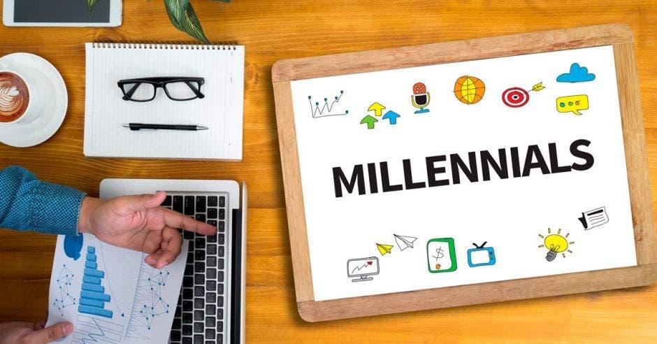 """Joven trabajando junto a una computadora, un cuaderno, una taza de café y un tablero que dice """"Millenials"""""""