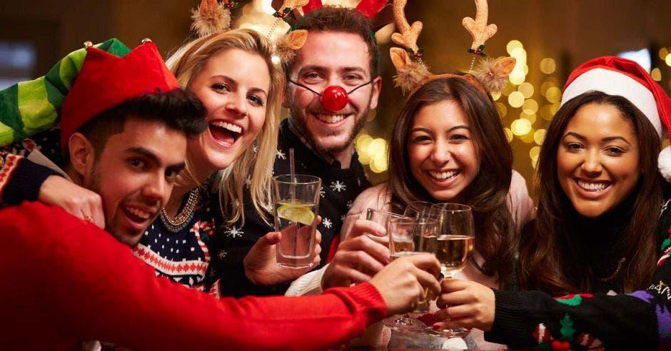 Una imagen de cinco amigos, dos hombre tres mujeres con sombreros navideños y brindando