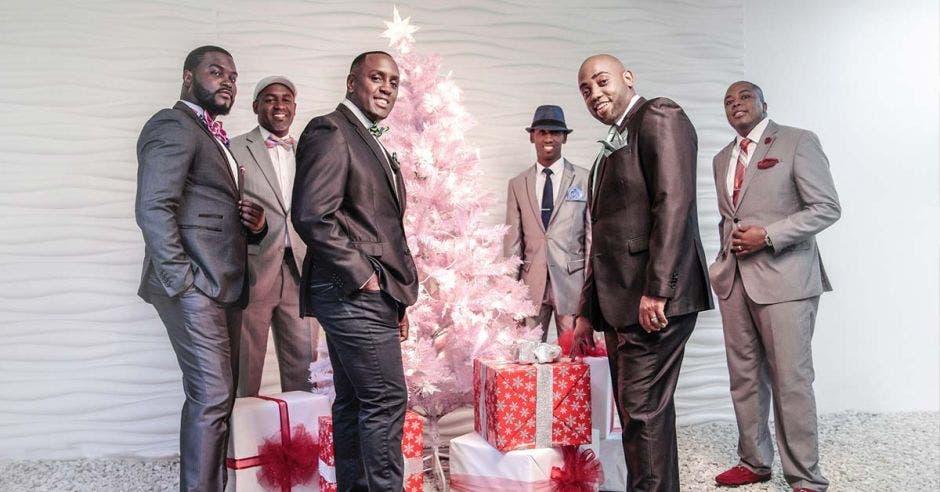 El grupo góspel MasterKey de seis integrantes de piel negra, vestidos de traje frente a un árbol de navidad