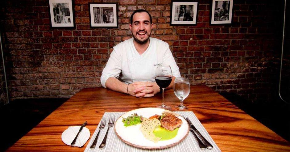El chef, hombre de pelo negro, con camisa blanca, sentado frente a uno de sus platillos y una copa de vino