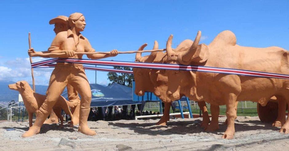 Escultura de un boyero, una boyera y su zaguate, junto a dos bueyes que halan la carreta.
