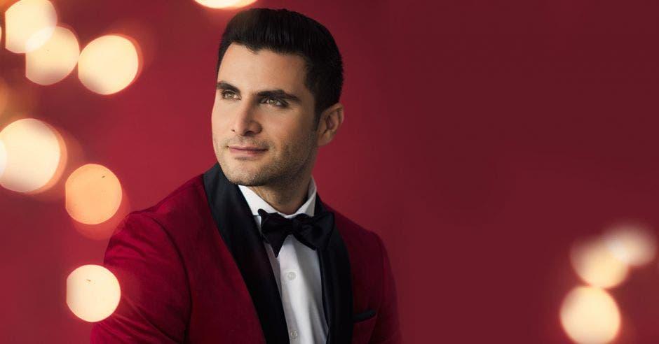 Joaquín Yglesias de traje rojo con un corbatín negro y camisa blanca