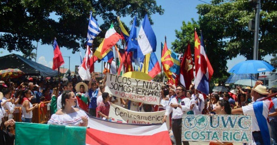 Varios niños vestidos con trajes tradicionales costarricenses con banderas de diferentes países y pancartas que dicen ticos y nicas somos hermanos