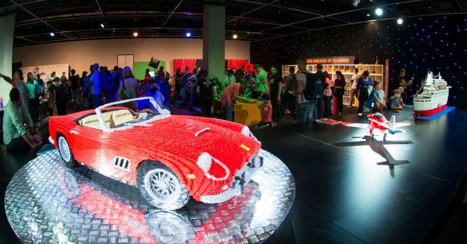 Un carro, un avión y un barco de legos en una exposición frente a decenas de personas