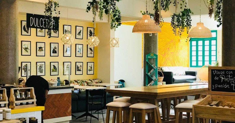 local con paredes amarillas, lámparas de paja, mesas de madera y cuadros de pájaron en una de las paredes