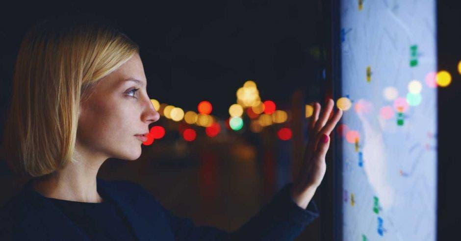 Una mujer manipula una pantalla táctil