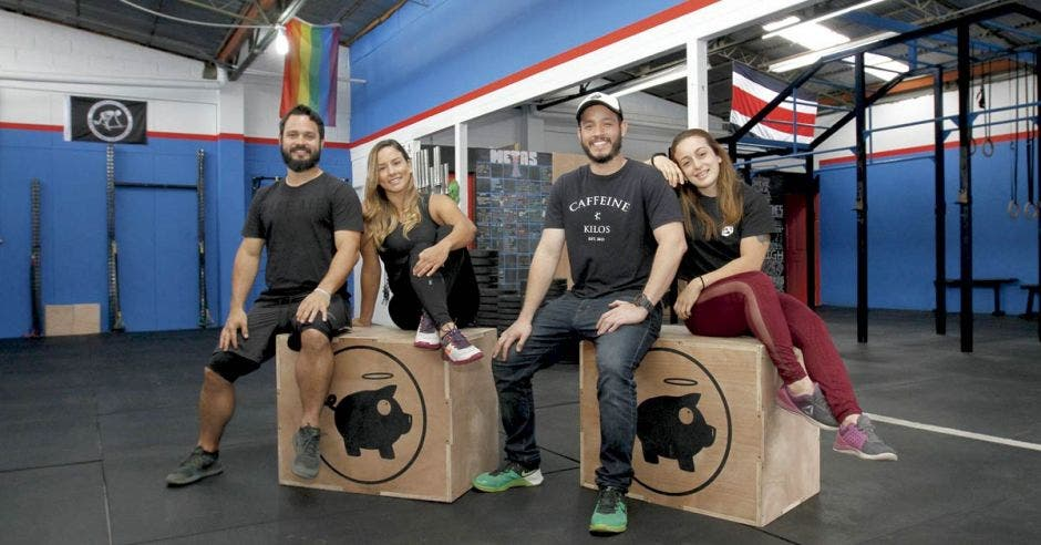 Sentados en dos cajas con el logo del gimnasio (Pancetta), se encuentran los dos socios del gimnasio junto a la fisioterapeuta, Ariela Méndez y la entrenadora, Daniela Chinchilla.