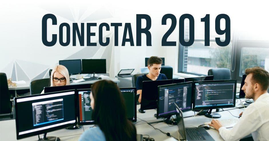 """Un grupo de jóvenes en un salón, programando en sus computadoras, Arriba en letras """"Conecta R 2019""""."""