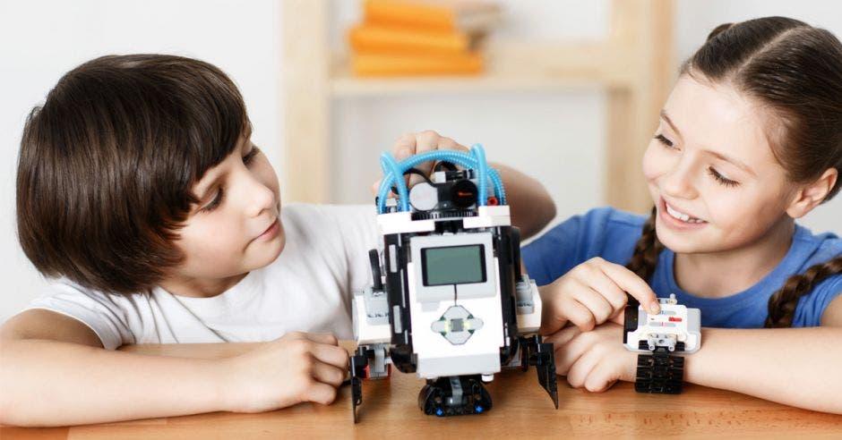 Un niño y una niña jugando con un robot.